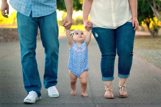 baby walking with two adultsholding hands