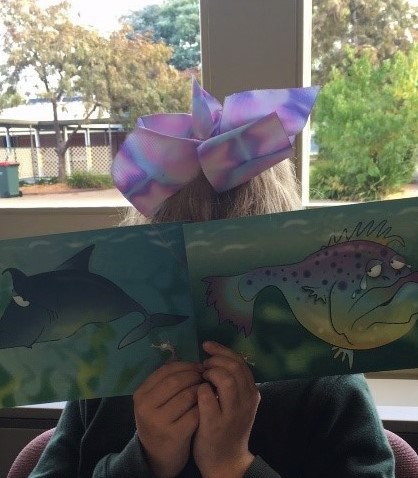 Child covering face with a funky fish feeling cards