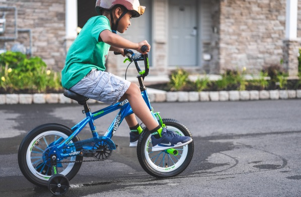 child riding bicycle with training wheels