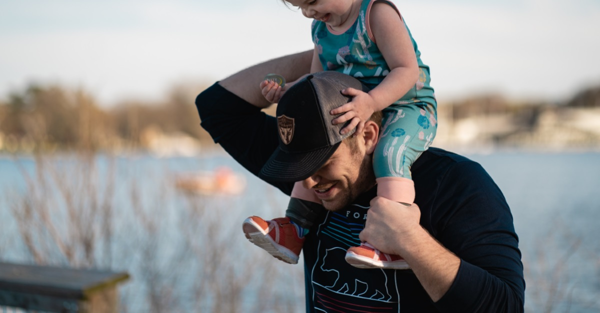 baby riding on man's shoulders with both having fun