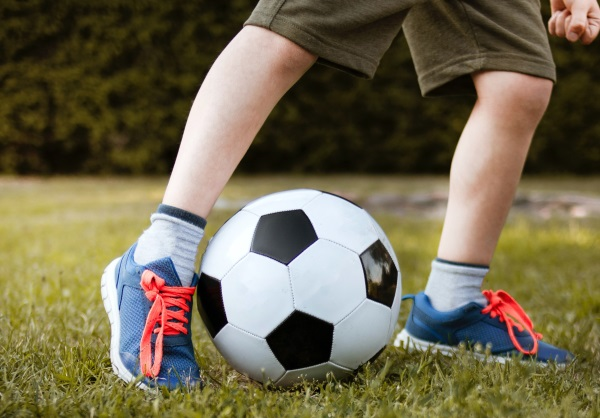 legs and feet of a boy as he kicks a soccer ball