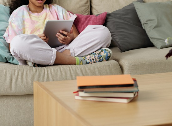 girl sitting on the couch looking at an ipad tablet