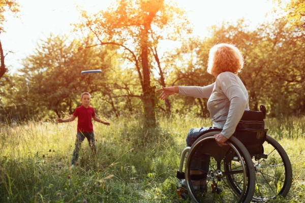 mother in wheelchair and boy throwing frisbee