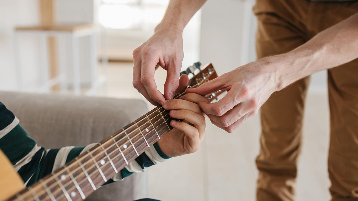 Adult teaching a young person how to play guitar in a home